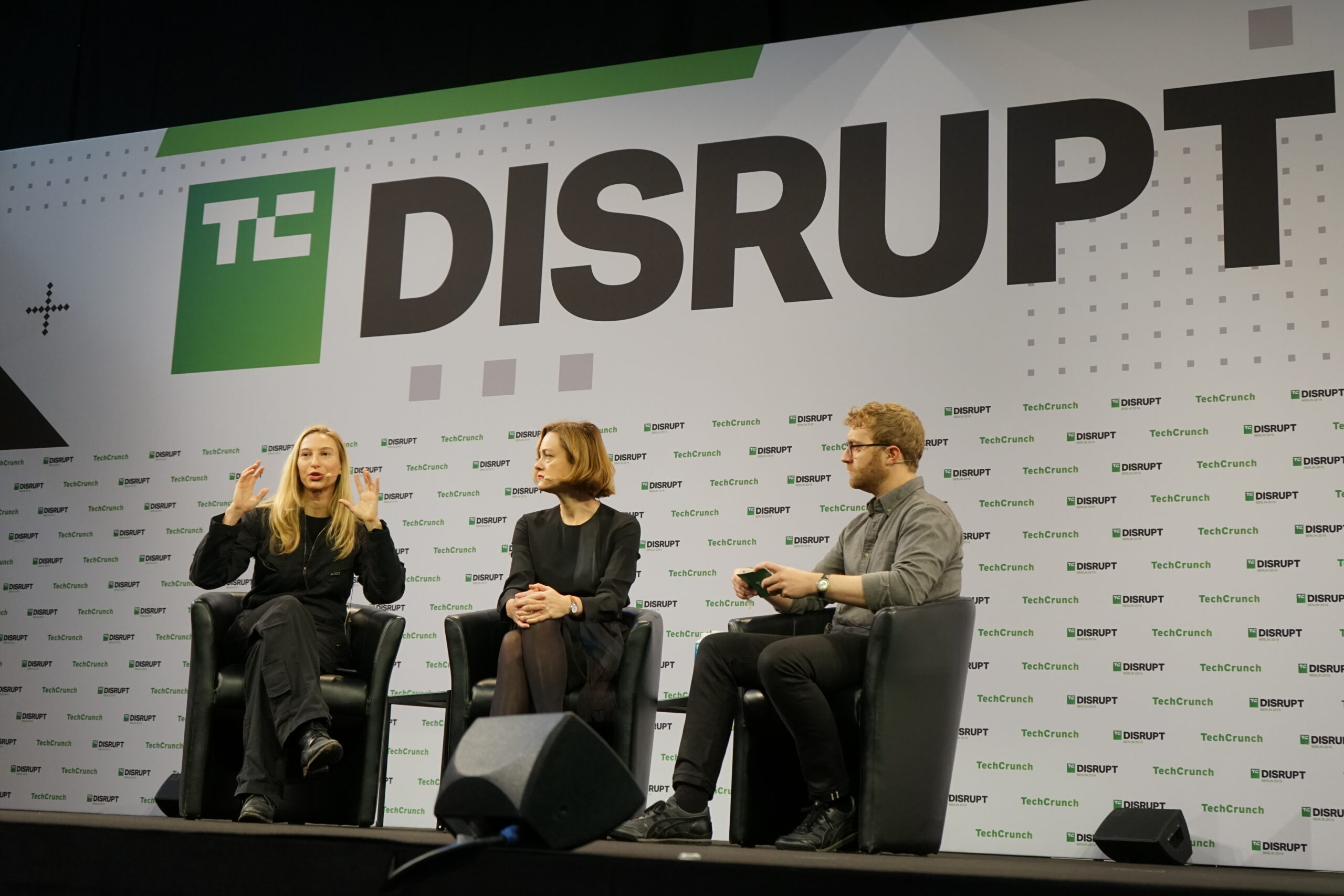 three people seated on stage at TC Disrupt