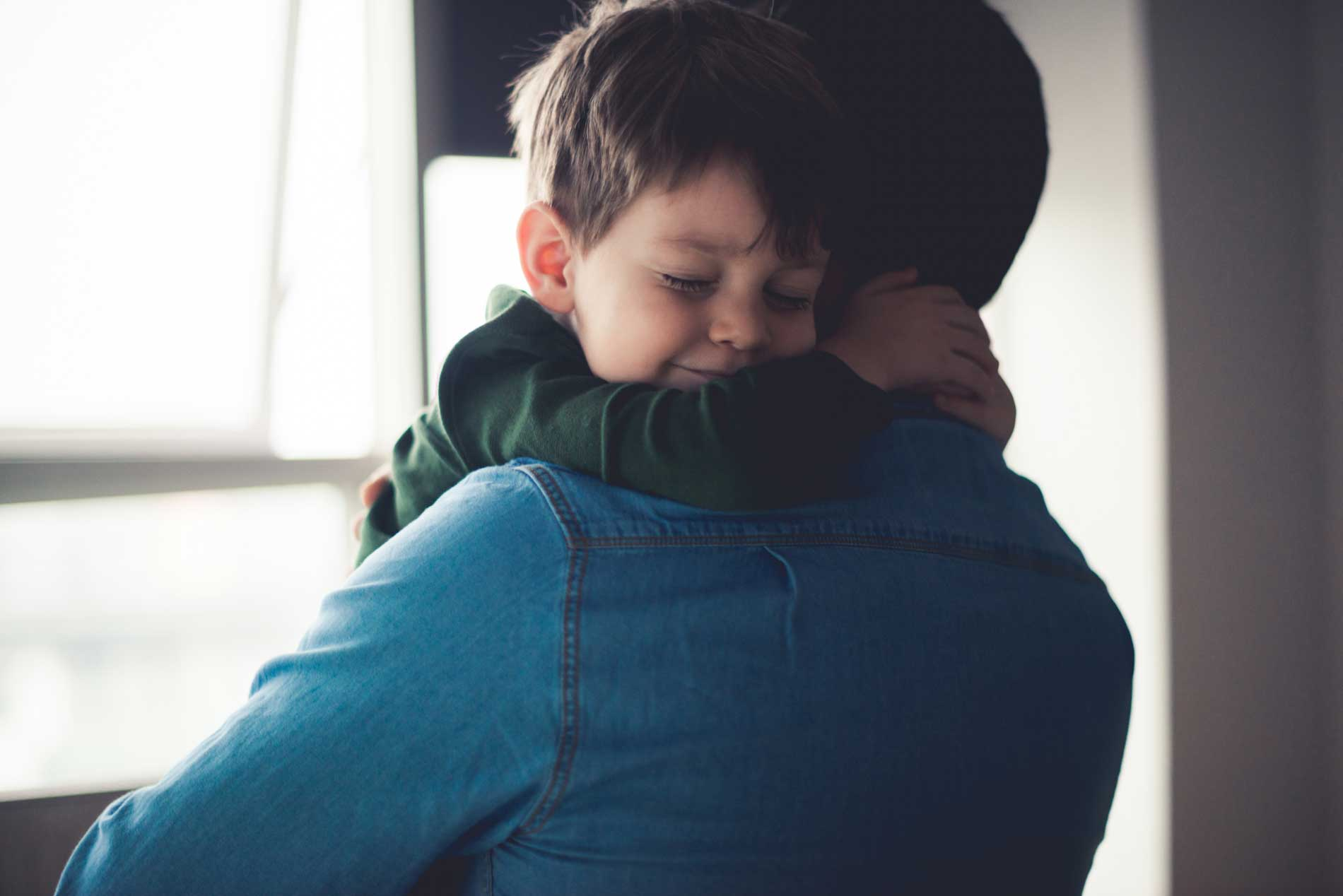 boy hugging father and smiling