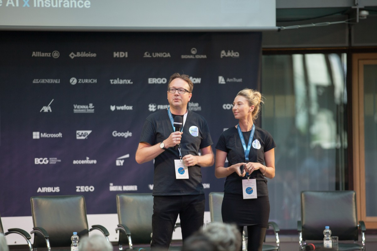 a man and woman standing on conference
