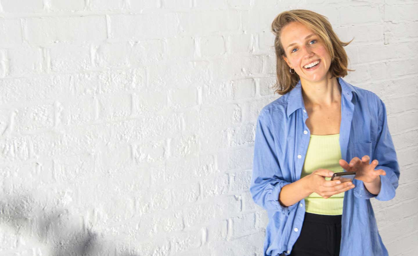 woman holding phone smiling happily